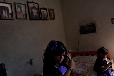 "A young girl from Ciudad Juarez prepares for her 15th birthday party, a coming of age party known as a ""quinceañera."" Her family spent most of their savings on making it a happy occasion. Her father had recently lost his job and was making ends meet by making repairs to homes in the neighborhood. Photo: Dominic Bracco II"